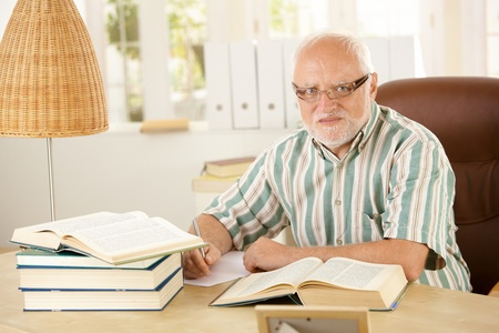 severity: Portrait of older man working at his study, taking notes, using books, looking at camera.