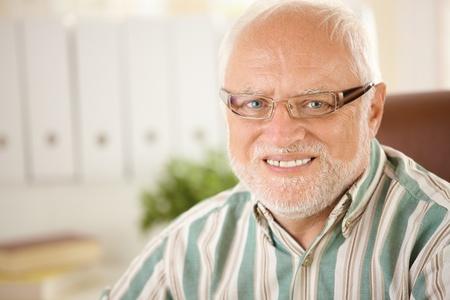 Closeup portrait of elderly man wearing glasses, smiling at camera. photo