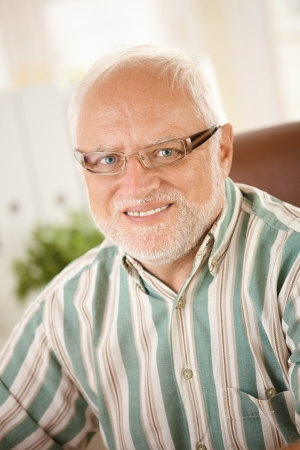 Portrait of senior man in glasses, looking at camera, smiling. photo