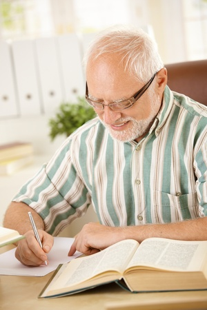 exercise book: White hair pensioner sitting at desk, writing letter at home, smiling.