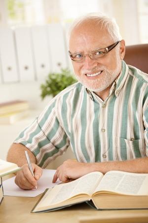 taking note: Ritratto di sorridente uomo anziano lavorando alla scrivania, prendendo le note, utilizzando i libri. Archivio Fotografico