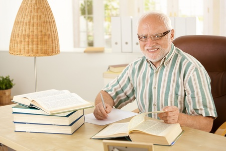 Elderly professor working in his study, taking notes, turning page, smiling at camera. photo