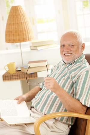 Happy pensioner reading at home, sitting in armchair, smiling at camera. photo
