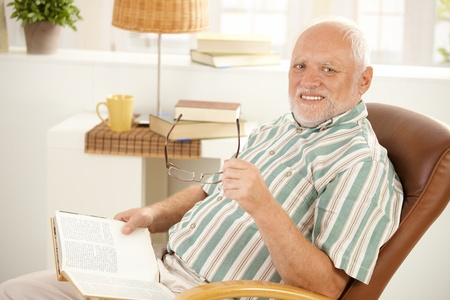 only one senior: Senior man reading book in armchair at home, holding glasses, looking at camera, smiling.