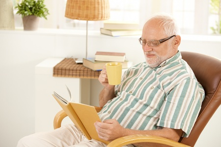 Smiling senior relaxing at home, reading book and drinking tea, sitting in living room armchair. photo