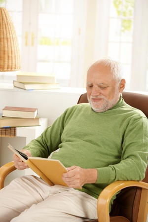 Older man sitting in armchair by window, relaxing at home, reading book, smiling. photo