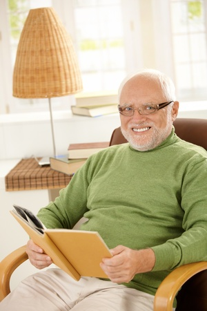 Portrait of happy pensioner relaxing at home, sitting with book in armchair, looking at camera, smiling. photo
