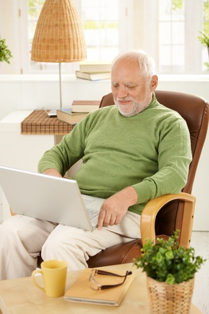 Smiling older man sitting in armchair using laptop computer at home. photo