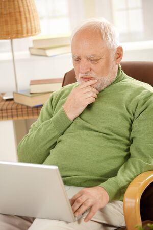 one senior adult man: Senior man sitting at home, looking at screen of laptop computer, thinking.