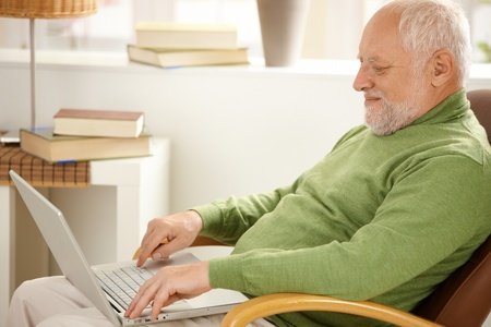 one mature man only: Smiling pensioner using laptop computer, sitting in armchair at home.