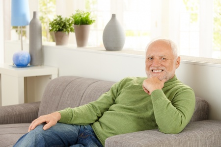 pensioners: Portrait of pensioner sitting on couch at home, smiling. Stock Photo