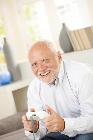 Senior man enjoying computer game, laughing, sitting at home. Stock Photo - 8748149