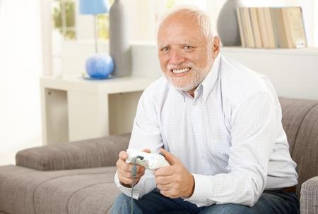 Modern pensioner playing computer game on sofa, smiling. photo