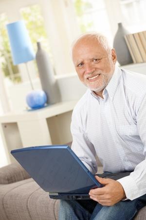 Senior man using laptop computer on sofa, looking at camera, smiling. photo