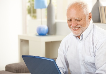 Portrait of aged man at home looking at laptop computer screen, smiling. Stock Photo - 8748107