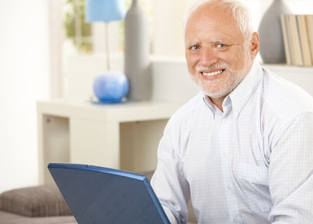 Portrait of senior man at home, having laptop computer, smiling at camera. photo