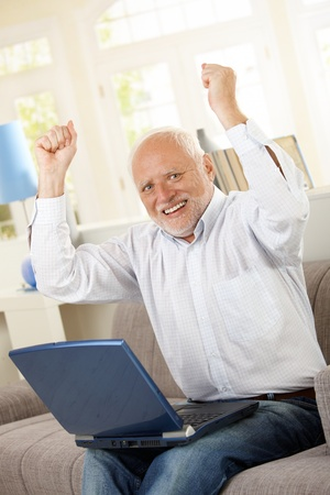 Happy old man sitting on sofa with laptop, raising arms and laughing, looking at camera. photo