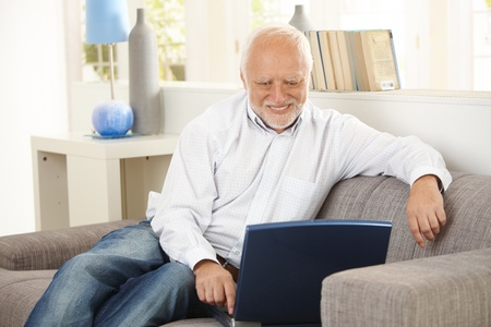 Older man sitting on sofa, smiling at computer screen at home. photo