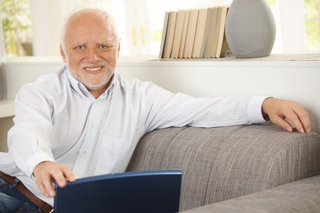 Portrait of elderly man sitting on sofa, holding laptop computer, smiling happily at camera. Stock Photo - 8748767