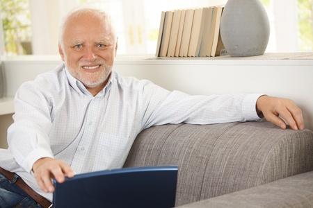 Portrait of elderly man sitting on sofa, holding laptop computer, smiling happily at camera. photo