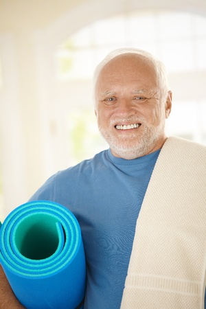 Active senior in sportswear holding polyfoam, smiling at camera. photo