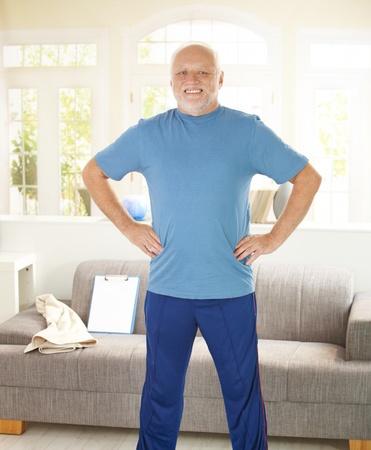 hombres haciendo ejercicio: Senior activo haciendo ejercicios en casa, en la sala de estar, sonriendo.