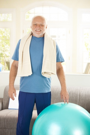 boomers: Active senior exercising with fit ball at home, smiling at camera.
