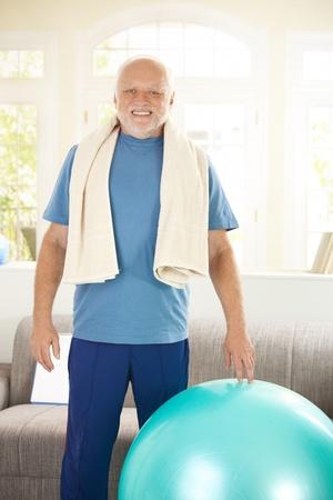 Active senior exercising with fit ball at home, smiling at camera. photo