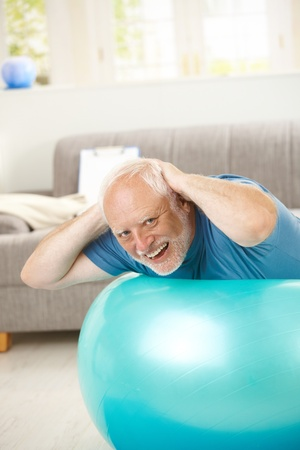 Happy active senior exercises on fit ball at home, looking at camera, laughing. photo