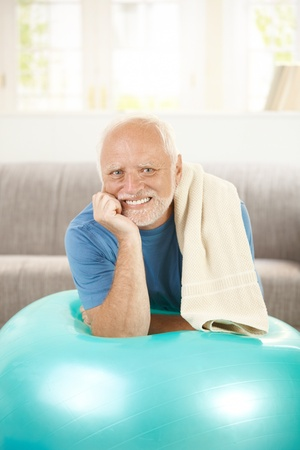 one senior man only: Portrait of active senior with fit ball, laying on exercise ball, smiling. Stock Photo