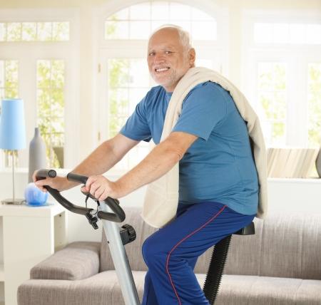 Senior hombre sonriendo en bicicleta fitness, ejercicio en el hogar, sonriendo a la cámara.
