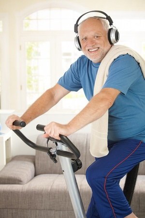 boomers: Sporty senior listening to music via headphones while exercising on stationary bike, at home, smiling at camera.