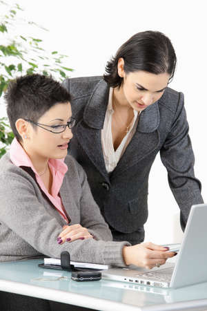 Happy young businesswomen working with laptop computer, smiling. photo