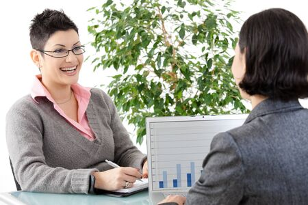 Young businesswomen having a business meeting, discussing business chatrs on laptop computer. Stock Photo - 8752494