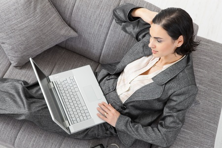 Young businesswoman sitting on sofa, working with laptop computer. Isolated on white background, overhead view. photo