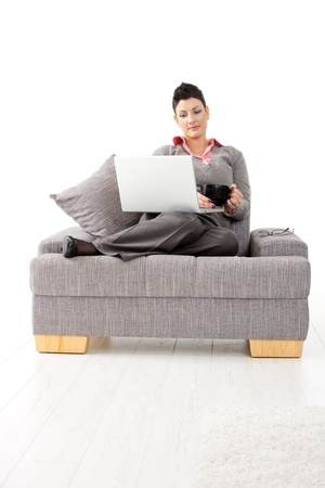 Casual young businesswoman sitting on sofa with laptop computer, holding a cup of tea. photo