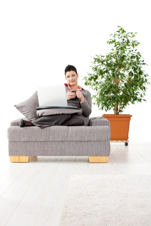 Young woman sitting on couch working on laptop computer at home, smiling. White background with green plant. Stock Photo - 8752487