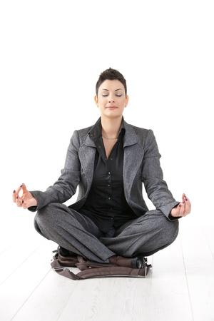 mujeres sentadas: Joven empresaria sentado en posici�n de loto de yoga en su caso de port�til, meditando con los ojos cerrados, aislados. Foto de archivo
