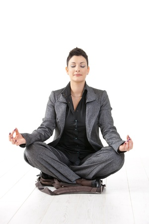 Young businesswoman sitting in yoga lotus position on her laptop case, meditating with closed eyes, isolated. photo