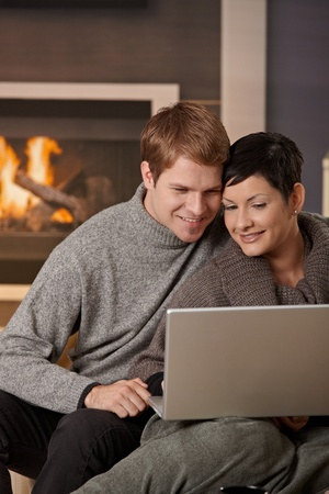 Young couple hugging on sofa at home in winter, using laptop computer, smiling. photo