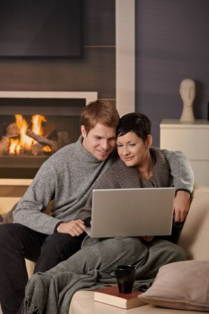 warm cloth: Young couple hugging on sofa at home in winter, using laptop computer, smiling.