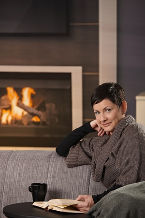 Woman sitting on sofa at home on a cold winter day, reading book, looking up at camera. photo