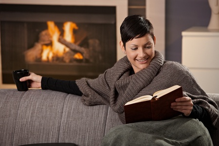 Woman sitting on sofa at home on a cold winter day, reading book. Stock Photo - 8752529