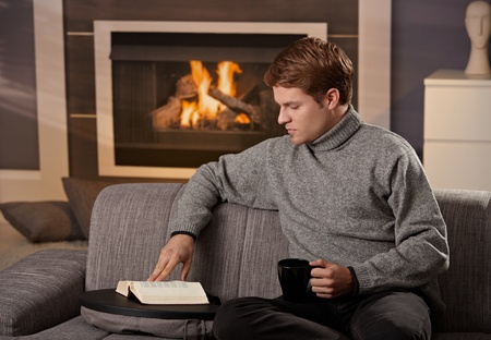 Young man sitting on sofa at home on a cold winter day, reading book in front of fireplace. Stock Photo - 8752539