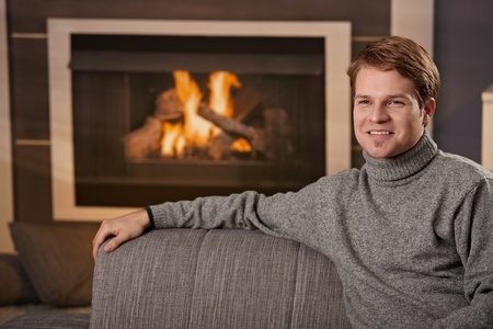 Young man sitting on sofa at home on a cold winter day in front of fireplace, smiling. photo