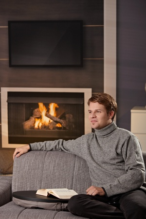Young man sitting on sofa at home on a cold winter day, reading book in front of fireplace. photo