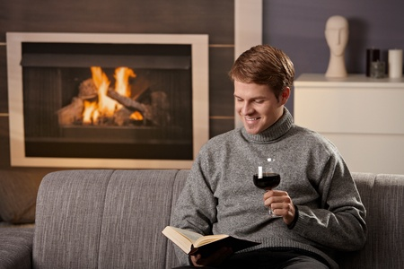 Young man sitting on sofa at home on a cold winter day, reading book in front of fireplace, tasting red wine. photo