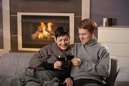 Young romantic couple sitting on sofa in front of fireplace at home, drinking red wine. photo