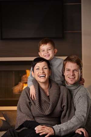 Happy family sitting on couch at home in a cold winter day, looking at camera, laughing. Stock Photo - 8752534