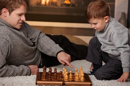 jugando ajedrez: Ni�o viejo padre y 4 a�os jugando al ajedrez en casa en un d�a fr�o de invierno.